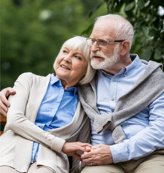 Old age couple sitting on a bench hand in hand